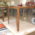 Vitrinas realizadas con cristal y rematadas con ángulos en las esquinas de aluminio color madera